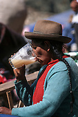 Paucartambo, Peru. Quechua woman drinking chicha from a large glass. Chicha is a fermented maize drink.