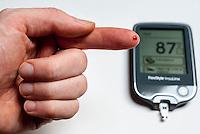 Glucometro per l'autocontrollo della glicemia (livello di zucchero nel sangue) nelle persone affette da diabete. La misurazione da una goccia di sangue presa da un dito --- Glucometer for monitoring of the glycemia (glucose amount in the blood) by people with diabetes. Measuring from a blood drop taken from a finger tip