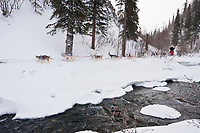 Karen Ramstead runs along the shelf ice near open water in the Dalzell Gorge on the trail to Rohn between Rainy Pass summit and Rohn during the 2010 Iditarod