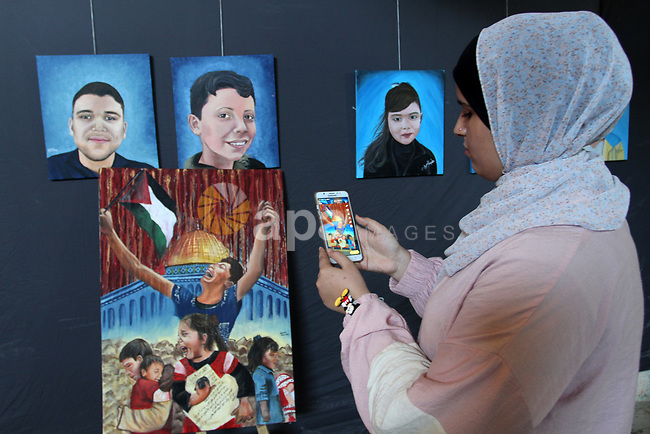Palestinians attend an art gallery contains 67 paintings depicting children who were killed during the recent 11-days conflict between Israel and Hamas, in Gaza city on August 10, 2021. Photo by Omar Ashtawy