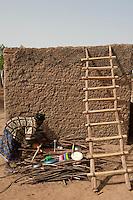 MALI, woman dry dishes infront of clay hut / MALI Frau trocknet Geschirr auf Feuerholz vor ihrer Lehmhuette