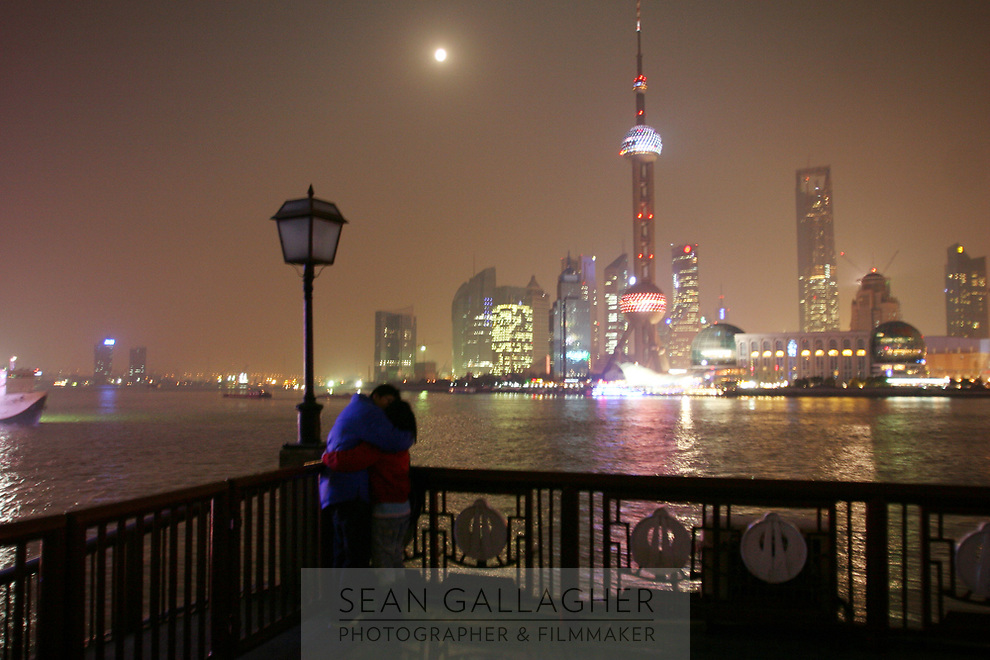 CHINA. Shanghai. A young couple on the Bund with the famous Pudong skyline behind them. Shanghai is a sprawling metropolis or 15 million people situated in south-east China. It is regarded as the country's showcase in development and modernity in modern China. This rapid development and modernization, never seen before on such a scale has however spawned countless environmental and social problems. 2008