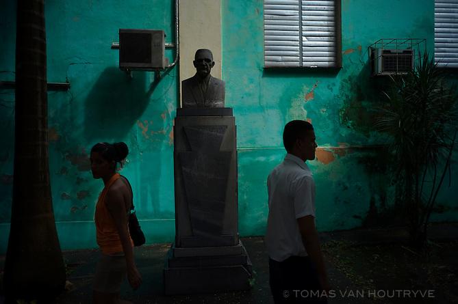 People walk past a bust of Dr. Joaquin Alvarez in the Mariano neighborhood of Havana, Cuba on Nov. 3, 2010.