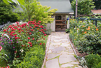 Red flowered bebalm Monarda, daylilies, sunflowers, bird house, garage, flagstone walkway path, in backyard landscaping with trees, shrubs, flowers