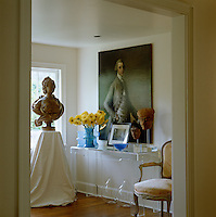 Old meets new in this anteroom in which an 18th century portrait hangs above a Perspex side table decorated with coloured glass and South American carved heads