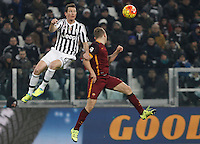 Juventus' Stephan Lichsteiner, left, and Roma's Daniele De Rossi jump for the ball during the Italian Serie A football match between Juventus and Roma at Juventus Stadium.