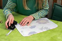 Kinder basteln ein Fensterbild mit Blüten, Mädchen locht die Ecken des Pergamentpapiers