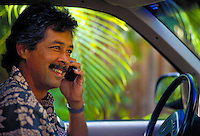 Honolulu businessman talking on cellular phone while stting in his car.