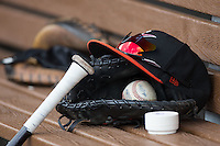 A Norfolk Tides cap sits on top of a glove in the visitor's dugout during the game against the Charlotte Knights at BB&T BallPark on June 7, 2015 in Charlotte, North Carolina.  The Tides defeated the Knights 4-1.  (Brian Westerholt/Four Seam Images)