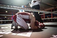 A boxer bends over and kneels on the ground in the ring at the London Irish Centre where the 'Carpe Diem' white collar boxing event is taking place. <br /> <br /> 'White-collar boxing' is a growing phenomenon amongst well paid office workers and professionals and has seen particular growth in financial centres like London, Hong Kong and Shanghai. It started at a blue-collar gym in Brooklyn in 1988 with a bout between an attorney and an academic and has since spread all over the world. The sport is not regulated by any professional body in the United Kingdom and is therefore potentially dangerous, as was proven by the death of a 32-year-old white-collar boxer at an event in Nottingham in June 2014. The London Irish Centre, amongst other venues, hosts a regular bout called 'Carpe Diem'. At most bouts participants fight to win. Once boxers have completed a few bouts they can participate in 'title fights' where they compete for a replica 'belt'.