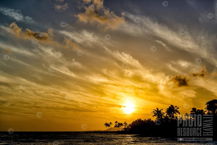 A glowing sunset through windswept clouds along Lawa'i Beach, Kaua'i.