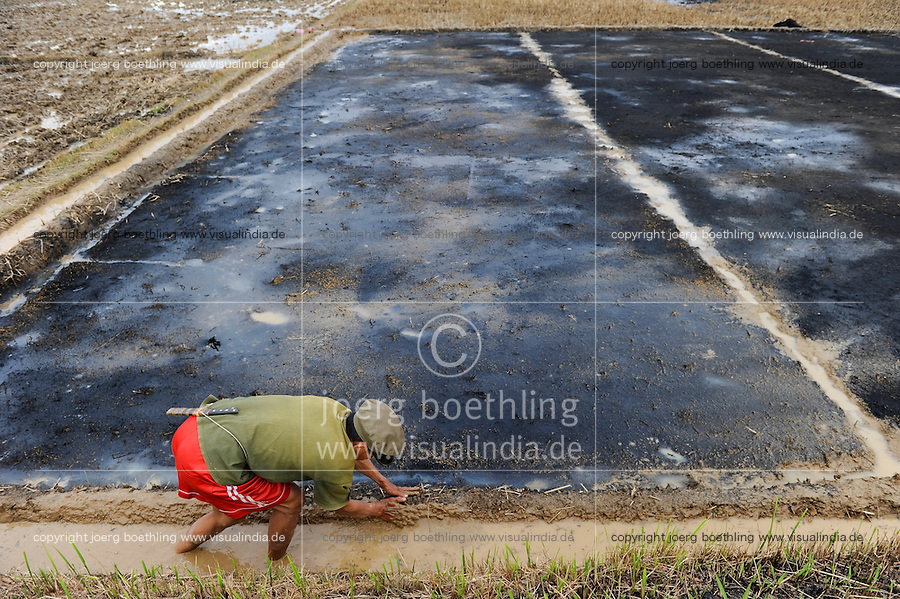 Laos, farmer cultivates paddy field, improvement of soil with compost and ash / Laos, Farmer bei Bodenbearbeitung, Verbesserung des Bodens mit Kompost und Asche