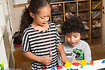 Education preschool 3-4 year olds boy and girl playing together naming shapes of blocks they have lined up on table