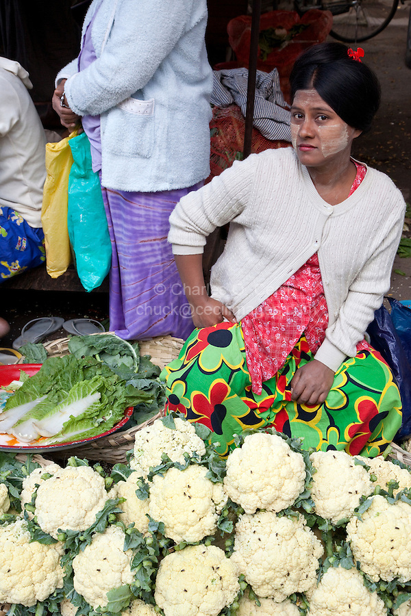 Myanmar, Burma, Mandalay.  Lady Selling Cauliflower in the Market.  She is wearing thanaka paste on her face, a cosmetic sunscreen.