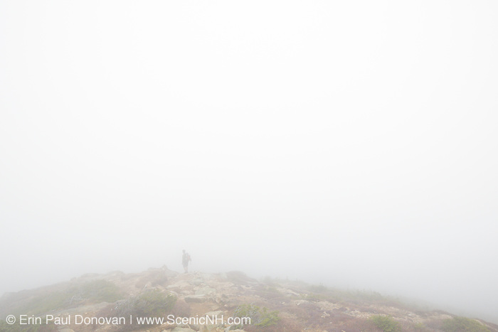 A hiker travels north on the Appalachian Trail (Franconia Ridge Trail), near Mount Lincoln, in the White Mountains of New Hampshire in foggy conditions during the autumn months.