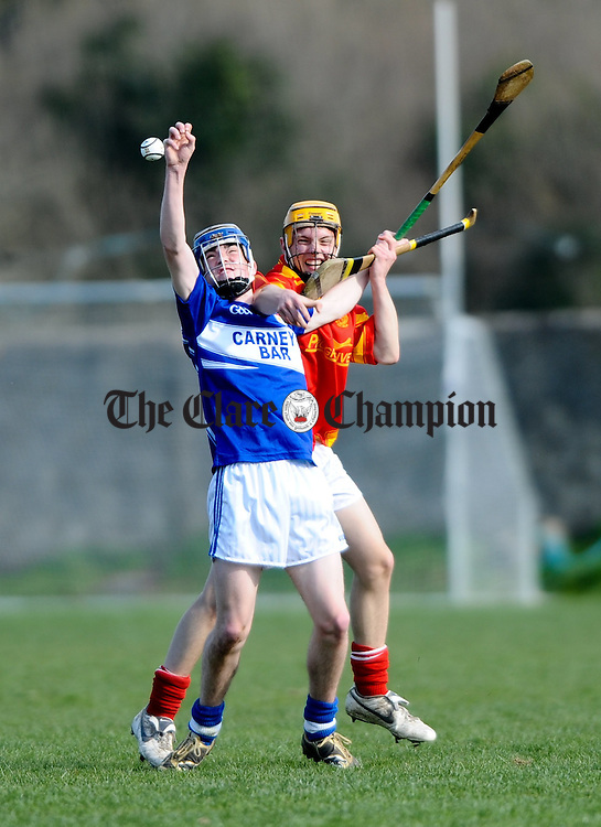 Niall Mc Guane of Kilmaley in action against Kevin Walsh of Smith O Briens during their U-21 hurling semi-final replay at Tulla. Photograph by John Kelly.