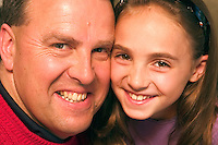 Girl posing cheek to cheek with her dad.