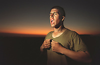 """SF.Marines.#43.db.08-22... Marine recruit Gilbert Escobedo stands yells in his underwear before bedtime, screaming the chant of """"Ready to fight, ready to kill, ready to die, but never will."""" Recruits were forced to scream this chant at the top of their lungs before being allowed to climb into their bivouac for the night to sleep. On this night and all of the third of four weeks of training at Camp Pendleton during this second phase, recruits slept outside....Photo by David Bohrer/FTT."""