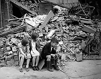 Children of an eastern suburb of London, who have been made homeless by the random bombs of the Nazi night raiders, waiting outside the wreckage of what was their home. September 1940