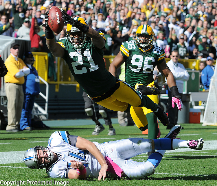 Green Bay Packers cornerback Charles Woodson dives into the end zone over Detroit quarterback Shaun Hill after his interception during the third quarter of the game at Lambeau Field in Green Bay, Wis., on Oct. 3, 2010.