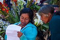 Chichicastenango, Guatemala.  Two Quiche (Kiche, K'iche') Women Looking at an Article on Steps of Santo Thomas Church, Sunday Morning.