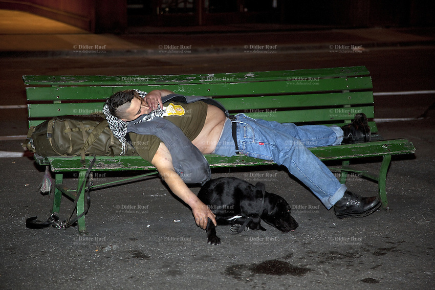 Switzerland. Geneva. Paquis neighborhood, known for its nightlife. A man is sleeping on a green bench. He is fully drunk. His black dog in lying on the ground. 24.03.12 © 2012 Didier Ruef