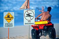Lifeguard patrolling on a four wheeler at sunset beach