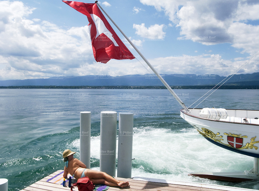 Switzerland. Canton Geneva. Anières. An old woman is sunbathing near the lake Geneva. The boat Savoie is mooring alongside the wharf of Anières. The Savoie is one of eight paddle wheel steamers, owned and ran by the Compagnie Générale de Navigation sur le lac Léman (CGN). The ship was built in 1914 during the Belle Époque's time  a period in European social history that began during the late 19th century and lasted until 1914.  10.07.09 © 2009 Didier Ruef
