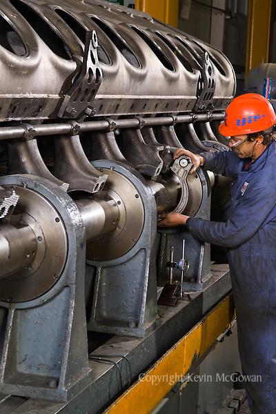 Worker testing train motor at locomotive repair factory