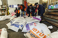 A crew of volunteers, including a group from the Alaska Military Youth Academy repack a musher's food drop bags which were too heavy at the Airland Transport facility in Anchorage, Alaska on Wednesday, February 17, 2016 just prior to Iditarod 2016