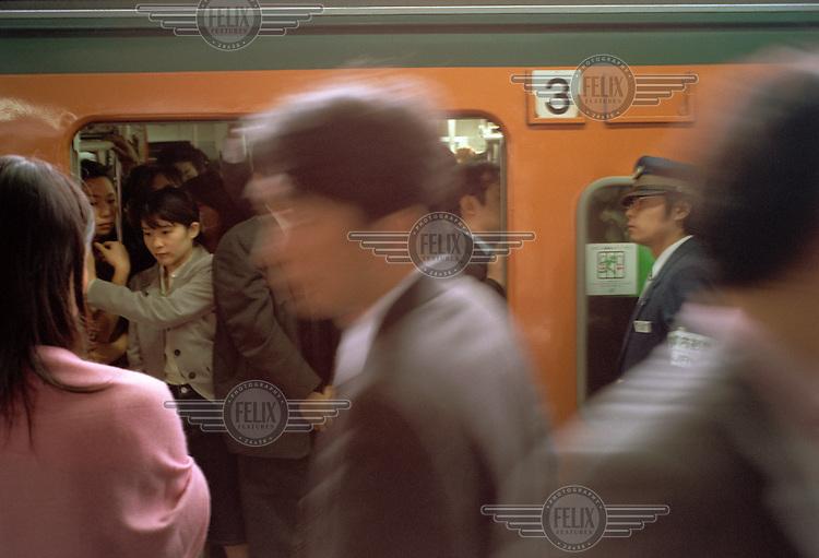 Commuters board an underground metro train.