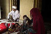 75-year-old Manganiyar artist sits down to eat his lunch while a family member is seen seen sitting next to him inside their house in Hamira village of Jaiselmer district in Rajasthan, India. Photo: Sanjit Das/Panos