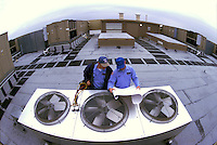 HVAC technicians consult blue prints before servicing rooftop compressor units on an office unit. Tennessee.