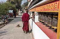 Nepal, Kathmandu, Swayambhunath.   A Young Buddhist Monk Spins Prayer Wheels as he Walks along the Wall around the Stupa at the Base of the Hill.
