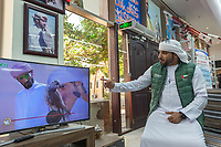 "United Arab Emirates (UAE). Dubai. Falcon & Heritage Sports Centre. The shop sells falcons and all equipment needed for falconry. An Emirati man looks on television at the UAE Falconers League competitions taking place at Dubai's Al Ruwayyah desert area. The man wears the traditional white thobe. A thawb (thobe, dishdasha, kandora) is an ankle-length garment, usually with long sleeves, similar to a robe, kaftan or tunic, commonly worn in the Arabian Peninsula. The headdress is called ghutrah. Falcons are birds of prey in the genus Falco, which includes about 40 species. Adult falcons have thin, tapered wings, which enable them to fly at high speed and change direction rapidly. Additionally, they have keen eyesight for detecting food at a distance or during flight, strong feet equipped with talons for grasping or killing prey, and powerful, curved beaks for tearing flesh. Falcons kill with their beaks, using a ""tooth"" on the side of their beaks. The United Arab Emirates (UAE) is a country in Western Asia at the northeast end of the Arabian Peninsula. 16.02.2020  © 2020 Didier Ruef"