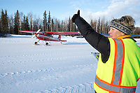 """Volunteer, Leslie Washburn gives the """"OK"""" thumbs up to Volunteer Iditarod Air Force pilot, Wes Erb as he taxis with a load of straw, musher drop bags, people food and HEET at the Willow, Alaska airport during the Food Flyout on Saturday, February 20, 2016.  Iditarod 2016"""
