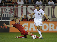 US defender Steve Cherundolo (6) is tripped up by Poland midfielder Adam Matuszczyk (15).  The U.S. Men's National Team tied Poland 2-2 at Soldier Field in Chicago, IL on October 9, 2010.