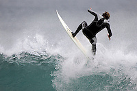 A surfer rides the lip of a wave.