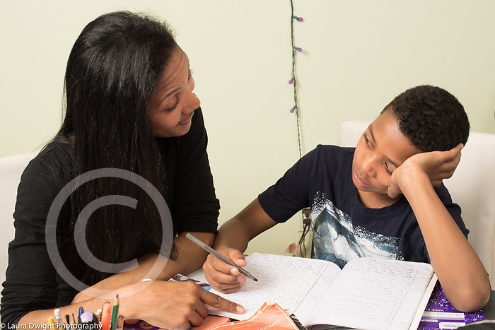10 year old boy at home with mother, doing homework, resting cheek on hand, looking discouraged, mother encouraging