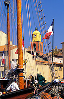 St. Tropez.  The town seen through the rigging of sailing ships.  Provence. France.