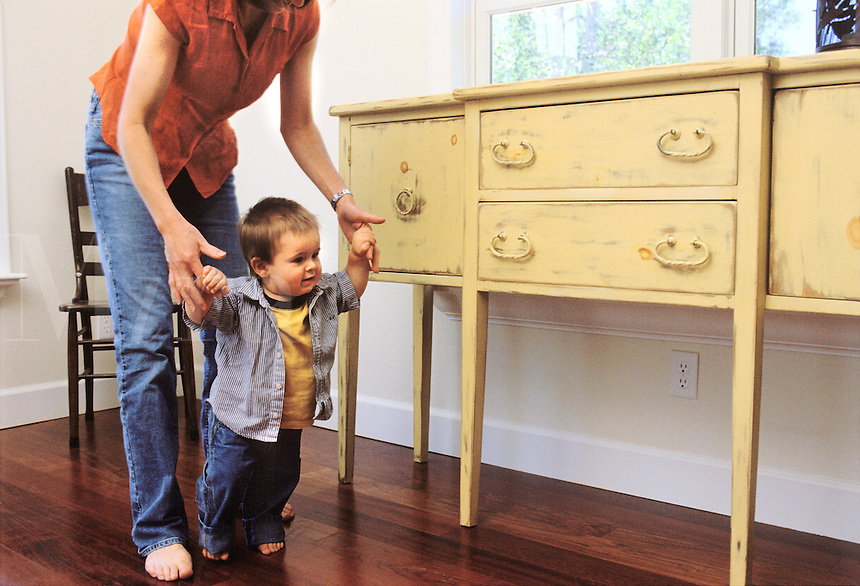 Toddler boy holding on to mom as he learns to walk