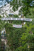 """Transparente """"#Leave No One Behind"""" und """"Wohnen ist keine Ware - Stopp Mietenwahnsinn"""" an der Hauswand des Haus Kohlfurterstrasse 46 Berlin-Kreuzberg. Das Haus ist Teil des sog. """"Block 89"""".<br /> 13.5.2020, Berlin<br /> Copyright: Christian-Ditsch.de<br /> [NUR FUER REDAKTIONELLE ZWECKE! Werbung nur auf Anfrage beim Fotografen. Inhaltsveraendernde Manipulation des Fotos nur nach ausdruecklicher Genehmigung des Fotografen. Vereinbarungen ueber Abtretung von Persoenlichkeitsrechten/Model Release der abgebildeten Person/Personen liegen nicht vor. NO MODEL RELEASE! Don't publish without copyright Christian-Ditsch.de, Veroeffentlichung nur mit Fotografennennung, sowie gegen Honorar, MwSt. und Beleg. Konto: I N G - D i B a, IBAN DE58500105175400192269, BIC INGDDEFFXXX, Kontakt: post@christian-ditsch.de<br /> Bei der Bearbeitung der Dateiinformationen darf die Urheberkennzeichnung in den EXIF- und  IPTC-Daten nicht entfernt werden, diese sind in digitalen Medien nach §95c UrhG rechtlich geschuetzt. Der Urhebervermerk wird gemaess §13 UrhG verlangt.]"""