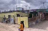 A girl walks past shacks in the township of Khayelitsha, in Cape Town. More than a quarter of a century after the end of apartheid, Cape Town remains highly segregated, and in townships like Khayelitsha, poverty and unemployment are still endemic.
