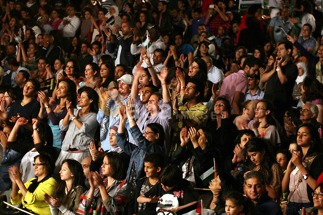Palestinians attend a concert by Egyptian soft rock band Wast El Balad (lit: Downtown) during the opening ceremony of the 13th Palestine International Festival, in the West bank city of Ramallah on July 4, 2011. Where organized by the Popular Art Center, the event will feature music, dancing and singing performances from several Arab and foreign countries. The festival runs from 04-09 July. Photo by Issam Rimawi