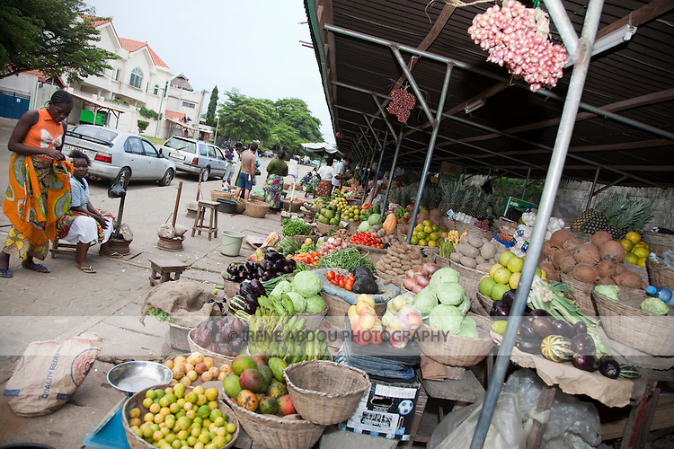 """Women sell fruits and vegetables at the """"Les Cocotier"""" market in Cotonou, Benin."""