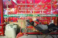 November 27, 2015, Yiwu China - A man sleeps outside a booth where Christmas  decorations on dispayed inside the Festival Arts section of the Yiwu International Trade Market. Yiwu International Trade Market is the world's largest whole sale market for small commodities. Christmas decorations are available for bulk purchase all the year round.Photo by Dave Tacon / Sinopix