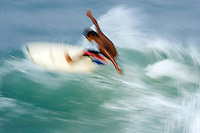 A blurred surfer in action on a big wave.