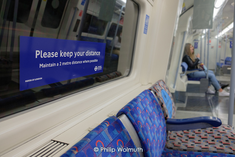 Please Keep Your Distnace sign in an akmisr empty  Jubilee Line underground train, London,  following the easing of Covid-19 lockdown measures.