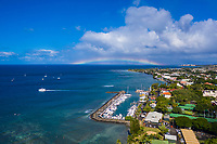 An aerial view of Maui's Lahaina Harbor with a rainbow overhead, with Lana'i in the distance.