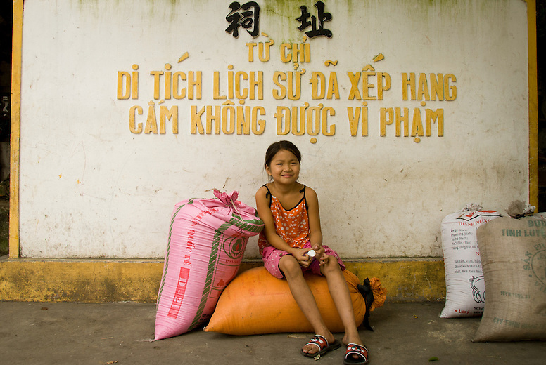 A girl sits on a bag of rice in the small village of Tho Ha just outside of Hanoi, Vietnam. At one time Vietnam didn't produce enough rice to feed itself, but with the introduction of the free market they've soared to become one of the top exporters in the world.  Vietnam's economic growth has been among the highest in the world in the past decade.